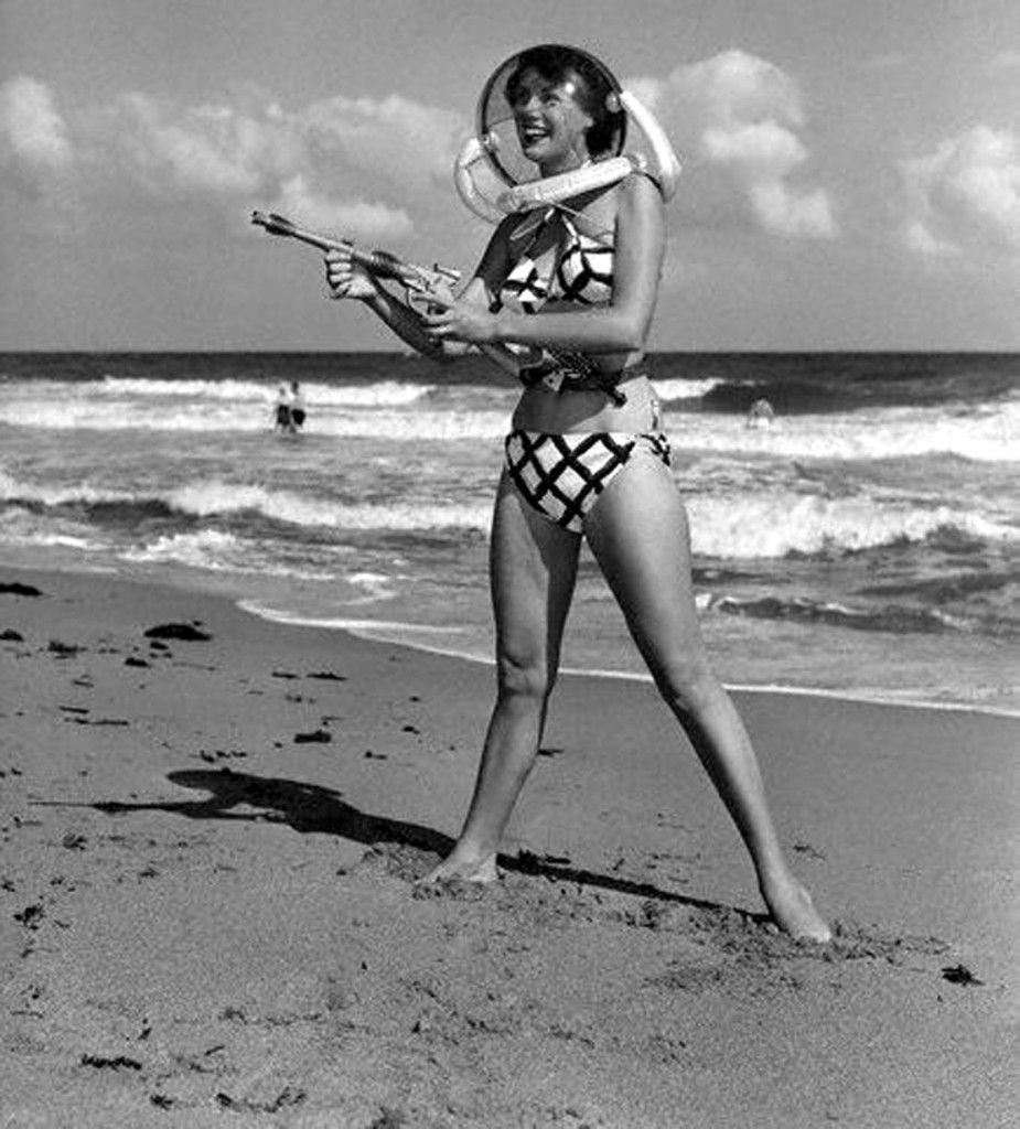 black and white photo of a girl in a bikini on a beach with a ray gun and space helmet. smiling.