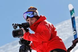 Camera operator filming while skiiing down snowy hill