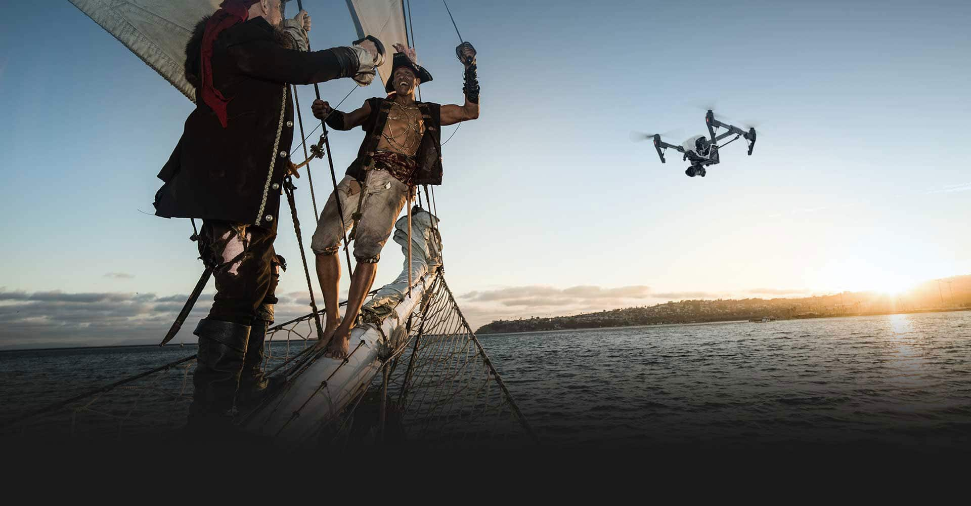 two men sailing with drone in background